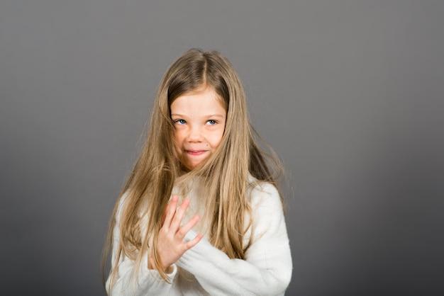 Feliz surpresa linda criança menina olhando para a câmera em fundo cinza. emoções humanas