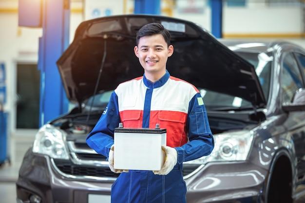 Feliz técnico ou mecânico de automóveis tranquilizando a bateria do carro no centro de serviço de reparo de automóveis.