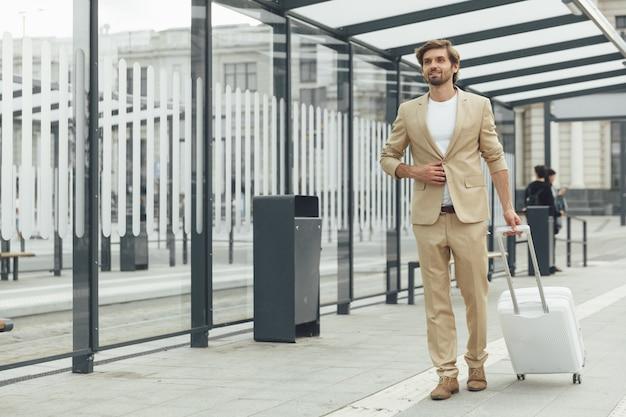 Feliz turista barbudo em um elegante terno à espera do transporte público na estação