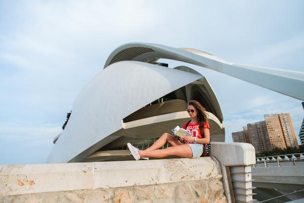 Feliz turista feminina com um mapa na cidade de artes e ciências em valência