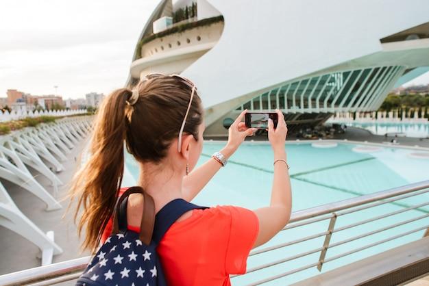 Feliz turista feminina é tirar uma foto na cidade de artes e ciências em valência