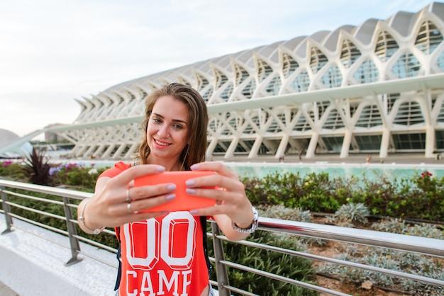 Feliz turista feminina está tomando uma selfie na cidade de artes e ciências em valência