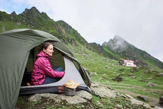 Feliz turista feminina sentada em uma tenda verde perto de um córrego da montanha em um terreno rochoso das montanhas.