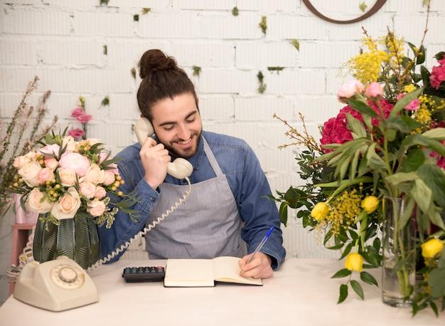 Feliz turista masculina levando a ordem no telefone em sua loja de florista
