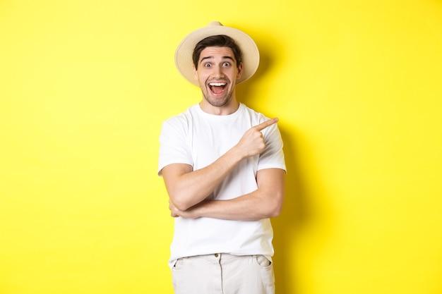 Feliz turista masculino no chapéu de palha apontando o dedo certo, mostrando a oferta promocional no espaço da cópia, fundo amarelo. copie o espaço