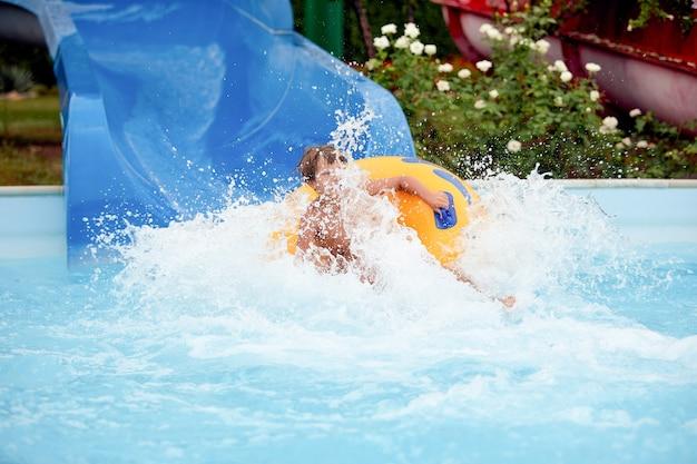 Feliz, um menino de 8 anos está andando no parque aquático em círculos infláveis em toboáguas com respingos