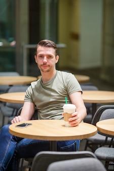 Feliz, urbano, homem jovem, café bebendo, em, europeu, cidade, ao ar livre