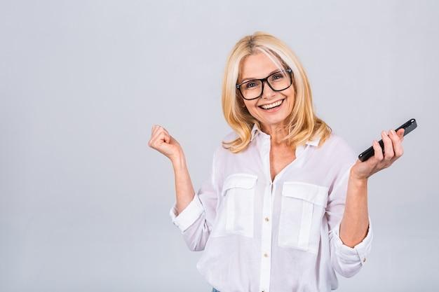 Feliz vencedor! foto de uma mulher idosa madura em êxtase louca usando smartphone impressionado nas redes sociais como feedback, vitória, levantar punhos, gritar, sim, isolado sobre fundo cinza branco