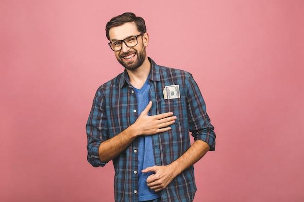 Feliz vencedor! homem rico novo na camisa quadriculado que guarda notas de dólar do dinheiro no bolso com surpresa isolada sobre o fundo cor-de-rosa.