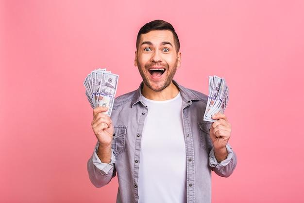 Feliz vencedor jovem rico casualmente segurando notas de dinheiro com surpresa