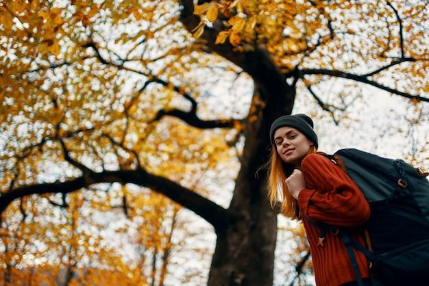 Feliz viagem com uma mochila em um suéter vermelho e jeans caminha no parque perto das árvores. foto de alta qualidade