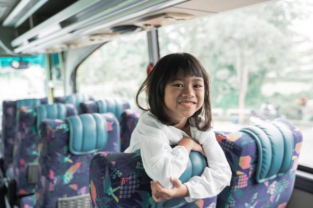 Feliz viagem de férias muçulmanas asiáticas em um ônibus com a família