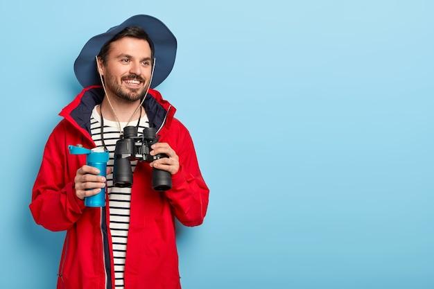 Feliz viajante explora um novo lugar, procura algo distante com binóculos, segura uma garrafa térmica azul com bebida, usa roupa casual