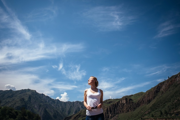 Feliz viajante feminino em uma camiseta branca contra as belas montanhas e o céu azul em dia ensolarado.