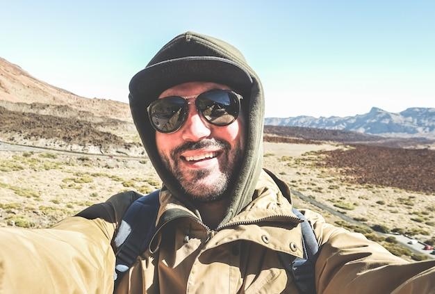 Feliz viajante masculino tirando selfie retrato com deserto de montanha