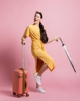 Feliz viajante posando com fundo rosa
