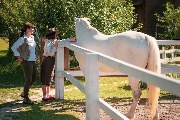 Feliz vida na fazenda. mãe e filha em roupas vintage ficam perto do paddock com uma linda