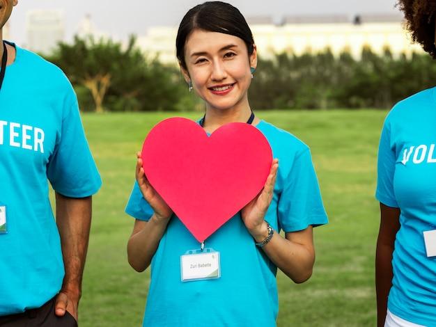 Feliz voluntário japonês com um coração