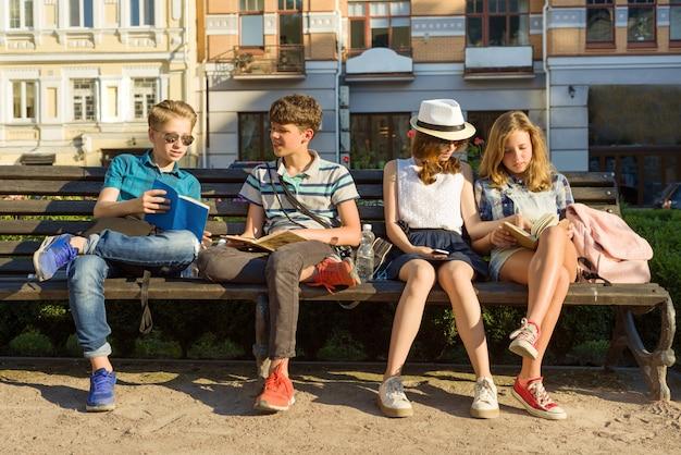 Felizes 4 amigos adolescentes ou estudantes do ensino médio estão se divertindo