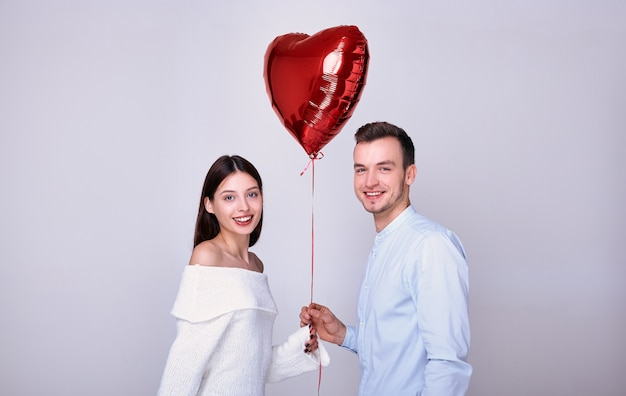 Felizes amantes com um balão vermelho em forma de coração.