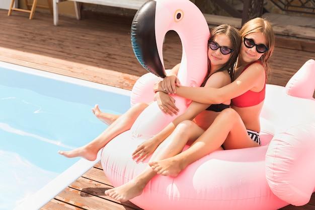 Felizes amigos abraçando a piscina nas proximidades