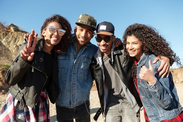 Felizes amigos africanos caminhando ao ar livre na praia, mostrando os polegares
