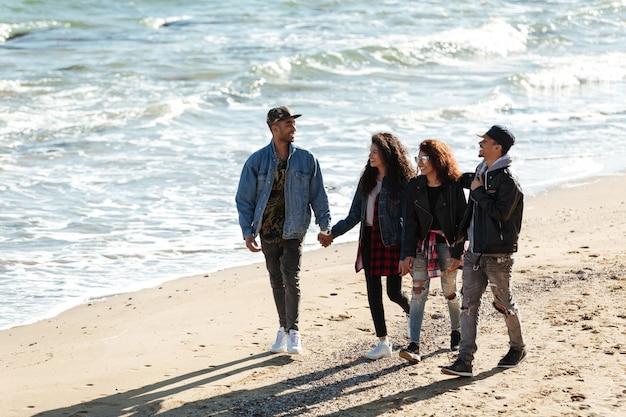 Felizes amigos africanos caminhando ao ar livre na praia