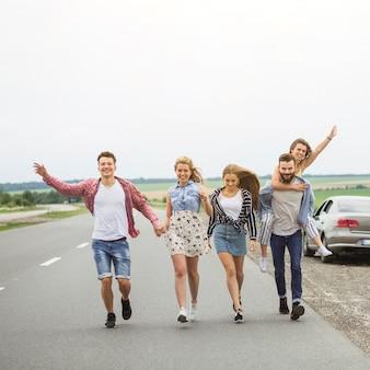 Felizes amigos andando na estrada juntos tirando sarro