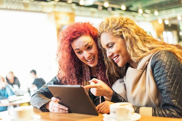 Felizes amigos atraentes no café, olhando para um tablet.