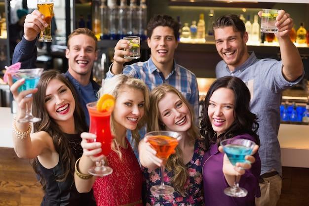 Felizes amigos beber cocktails juntos no bar