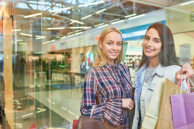 Felizes amigos bonitos andando sobre shopping
