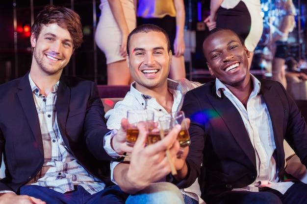 Felizes amigos brindando com álcool