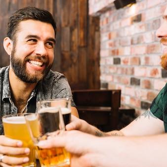 Felizes amigos brindando copos de bebidas alcoólicas em bar