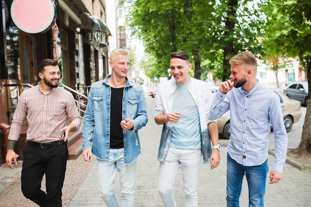 Felizes amigos caminhando juntos na calçada