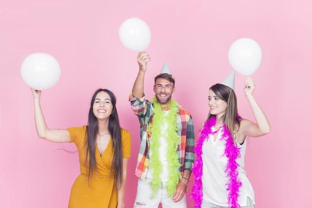 Felizes amigos com balões brancos em fundo rosa