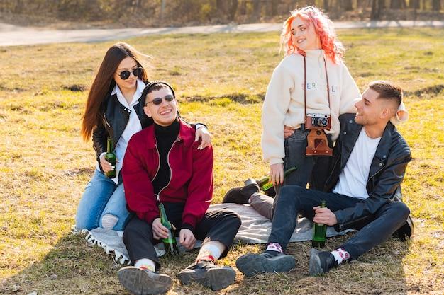 Felizes amigos com cervejas se divertindo juntos na festa ao ar livre