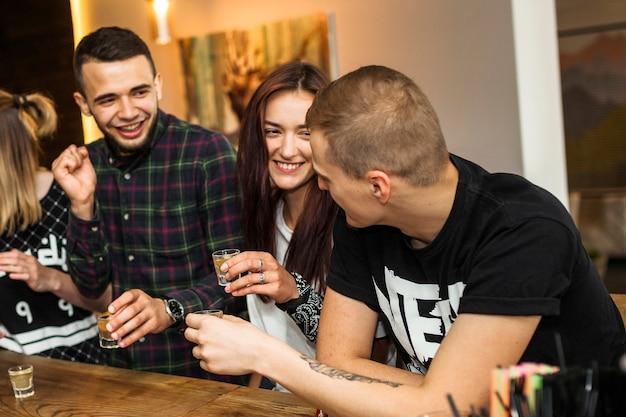 Felizes amigos desfrutando de beber tequila no bar