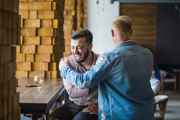 Felizes amigos do sexo masculino reunião no restaurante