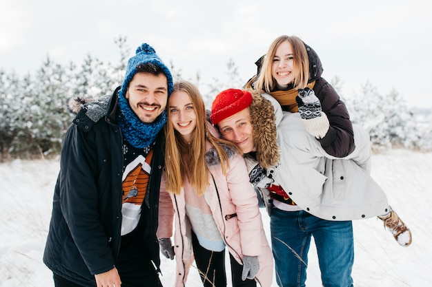 Felizes amigos em pé na floresta de inverno