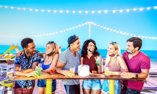 Felizes amigos multirraciais bebendo no bar de praia usando máscaras