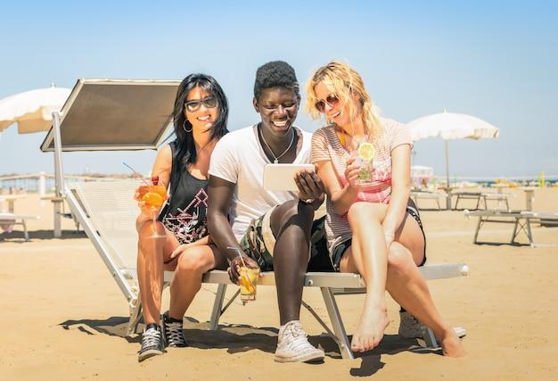 Felizes amigos multirraciais beber cocktails com tablet na praia