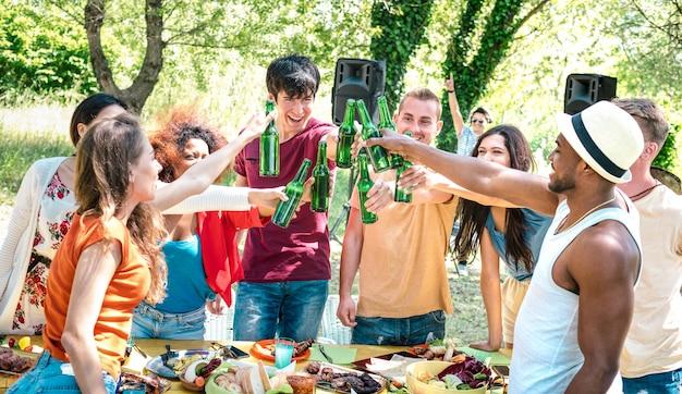 Felizes amigos multirraciais brindando cerveja na festa de churrasco no jardim