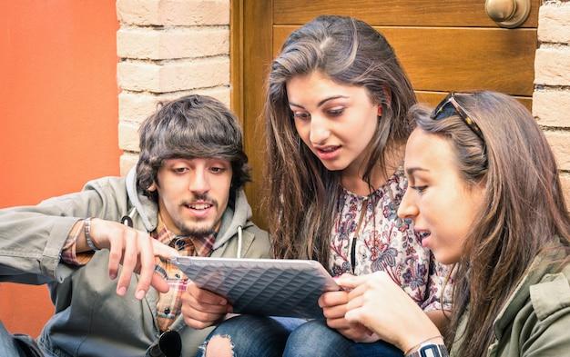 Felizes amigos se divertindo com tablet digital moderno
