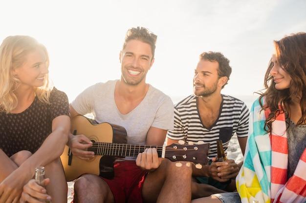 Felizes amigos se divertindo enquanto está sentado na areia