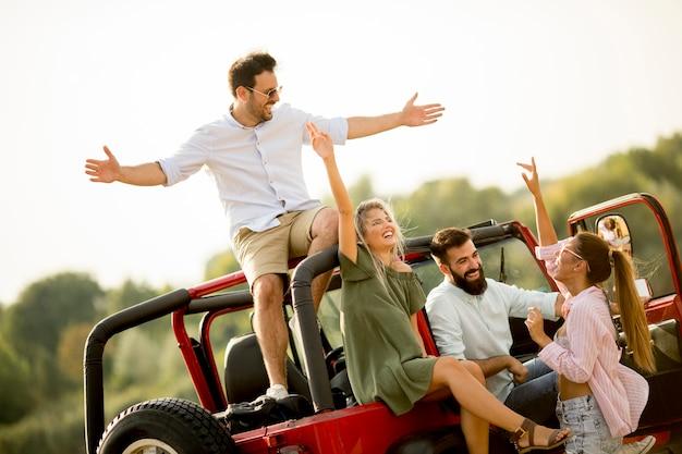 Felizes amigos se divertindo no carro conversível em férias