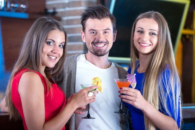 Felizes amigos segurando copos com cocktails no bar.