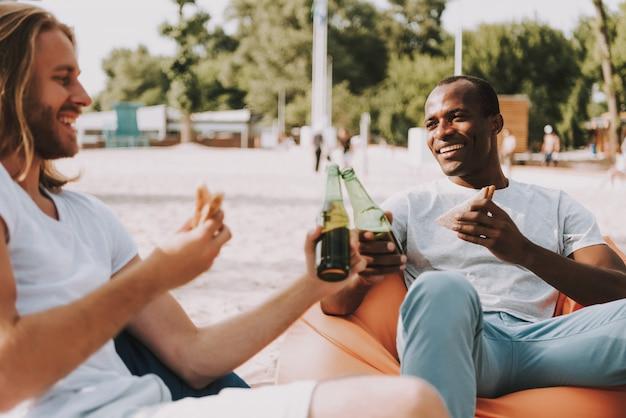 Felizes amigos têm comida e bebida na praia.