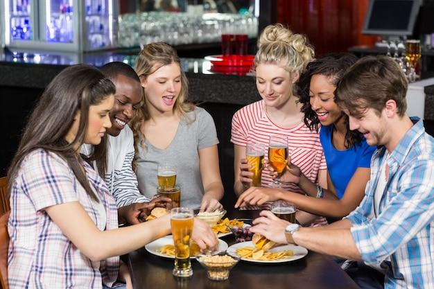 Felizes amigos tomando uma bebida e hambúrguer