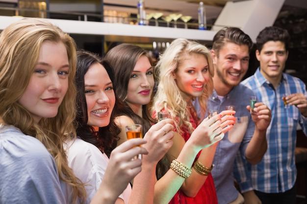 Felizes amigos tomando uma bebida juntos no bar