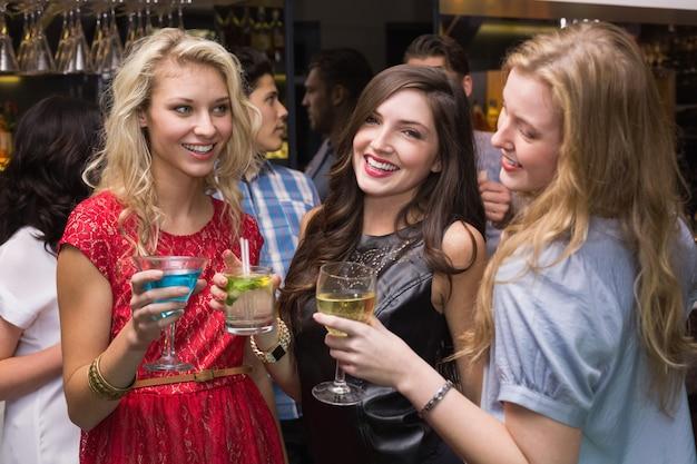 Felizes amigos tomando uma bebida juntos